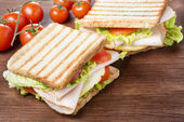 Sandwiches on wooden table — Stock Photo