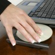 Woman&amp;#039;s hand placing dvd into laptop computer at desk - Stockfoto