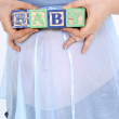 Blocks Spelling Baby Above Expecting Mom's Belly - Stock Photo