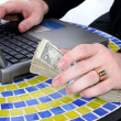 Stock Photo: Cash In Hand Resting On Table Top Near Laptop