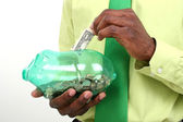 Businessman Putting One Dollar Bill In Green Piggy Bank — Stock Photo
