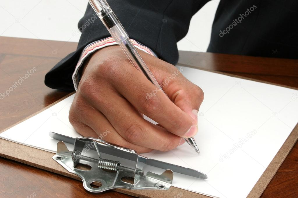 African American male hand writting on clipboard with pen.  Stock Photo #12772225