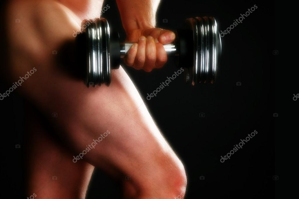 Nude male model with dumbbell over black. — Stock Photo #12772574