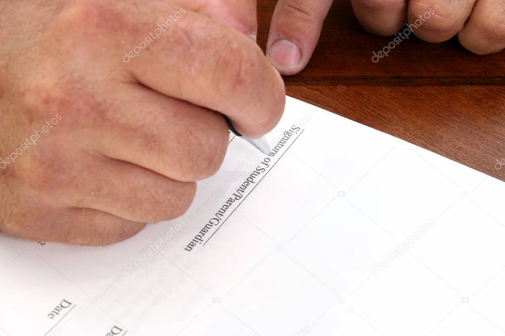 Man&#039;s hand signing contract. Line reads: Signature of Student, Parent, Guardian.  Stock Photo #12773025
