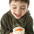 Foto Stock: Boy Eating Carrot Cupcake