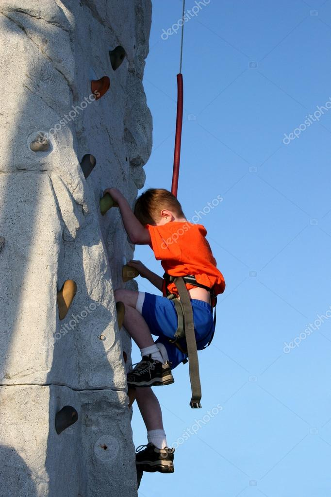 Young boy climbing a rock wall outside.    Stock Photo #12821409