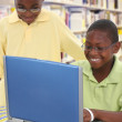 Foto Stock: Two Handsom Black Students at Laptop in School Library