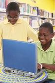 два красивых черный студентов в ноутбук в школьной библиотеке — Стоковое фото