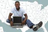 Jovem atraente sentada no chão com o computador portátil — Fotografia Stock