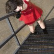 Beautiful Young Woman In Red Vinyl Dress On Fire Escape — Stock Photo #13120575