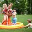 Boys and girl play with dad in the kiddie pool with water guns — Stock Photo