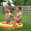 Backyard family fun in the kiddie pool. - 图库照片