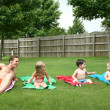 Children on towels with dad in the backyard - Stock Photo