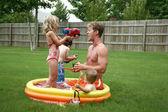 Backyard family fun in the kiddie pool. — Stock Photo