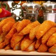 Baked battered spicy seasoned potato wedges in kitchen. - Stock Photo