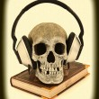 Audiobook Concept Human Skull with Headset on Book, Scary, Haunt - Stock Photo
