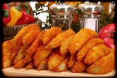 Baked battered spicy seasoned potato wedges in kitchen. — Zdjęcie stockowe