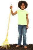 Krásná černá dívka dítě s hrábě stojící ve špíně — Stock fotografie