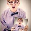 Adorable geeky teen boy holding electric notepad with photo of s — Stock Photo #28812299