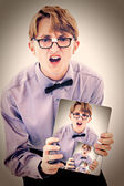 Adorable geeky teen boy holding electric notepad with photo of s — Stock Photo