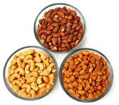 Three glass bowls filled with cashews, salted roasted almonds an — Stok fotoğraf