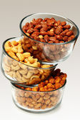 Three glass bowls filled with cashews, salted roasted almonds an — Stock Photo