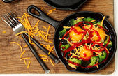 Uncooked Raw Eggs in Skillet with Brocolli, Cheese and Sriracha — Stock Photo