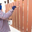 Construction worker is painting wooden fence — Foto Stock
