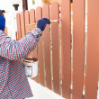 Construction worker is painting wooden fence — Foto de Stock