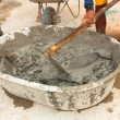 Builder worker during using hoe to mix wet cement — Foto Stock