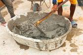 Trabajador constructor durante usar azada para mezclar cemento mojado — Foto de Stock