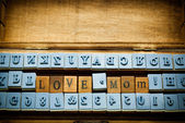 love mom spelling with rubber stamp in wood box — Stock Photo