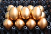 Golden eggs on black package — Stock Photo