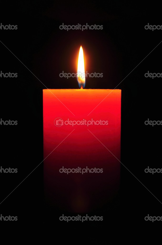 Burning large orange candle on a black background — Stock Photo #12453621