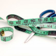 Green measuring tape and scissors — Stock Photo