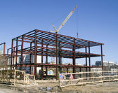 Building under construction and building crane — Stock Photo