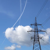 Jet-traces in the sky near power transmission line — Stock Photo
