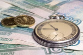 Vintage watch and coins on banknotes — Stock Photo