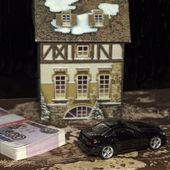 The toy car and cottage and a pile of money — Stock Photo