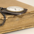 Stock Photo: Old watch and tattered book