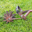 Old garden cultivator on green grass — Stock Photo #47193967
