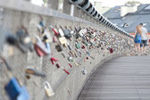 A young couple on the padlocked bridge — Stock Photo