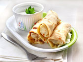 Stuffed crepes with sour cream — Stock Photo