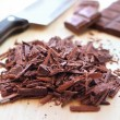 Chopped bar of dark chocolate on wooden background — Foto Stock