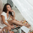 Gorgeous young brunette writer sitting on the bed — Stock fotografie