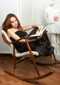 Portrait of attractive teenage girl in rocking-chair with book — Stock Photo