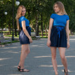 Nice young woman in blue short skirt with her twin — Stock Photo