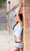 Nice young woman in jeans suit near brick wall — Stock fotografie