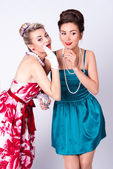 Two beautiful girls in a vintage dress telling tales — Стоковое фото