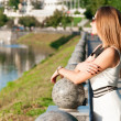 Nice young woman resting near a river — Stock Photo #35555009